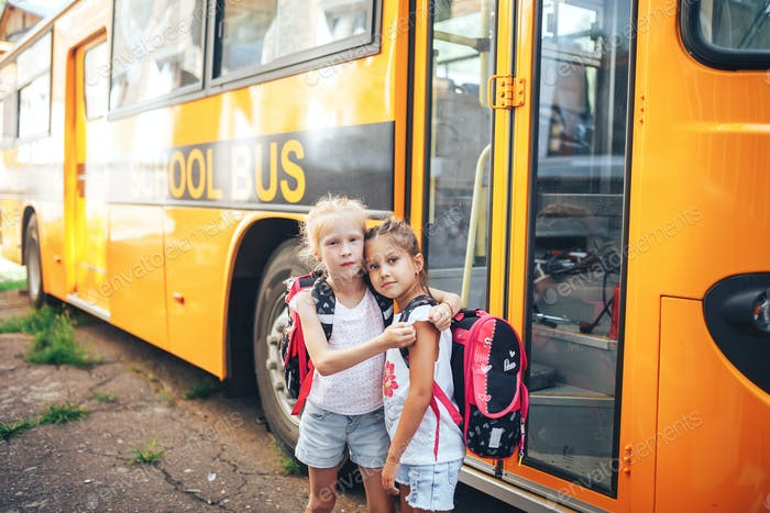 Schoolgirls with backpacks on the background of a school bus, back to school