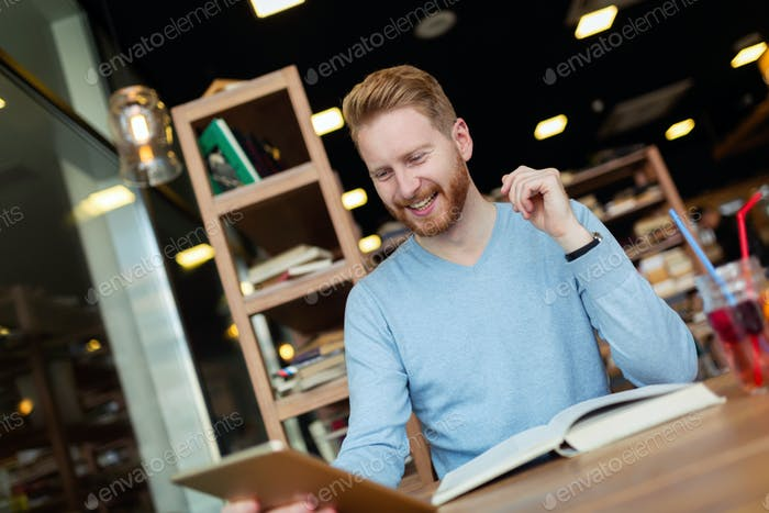 Young man using digital tablet in coffee shop