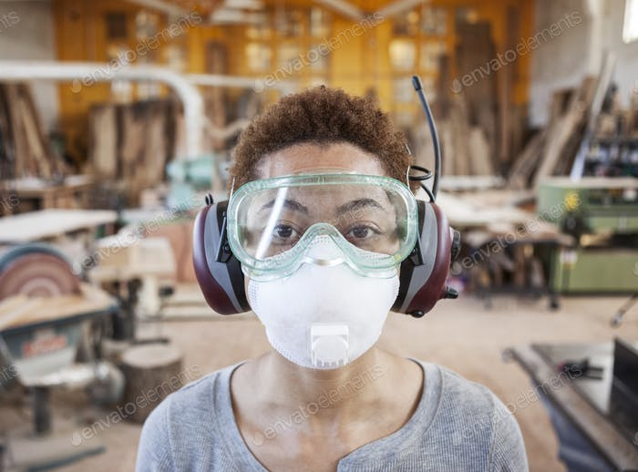 Close up view of black woman factoy worker wearing safety glasses and dust nose mask in a