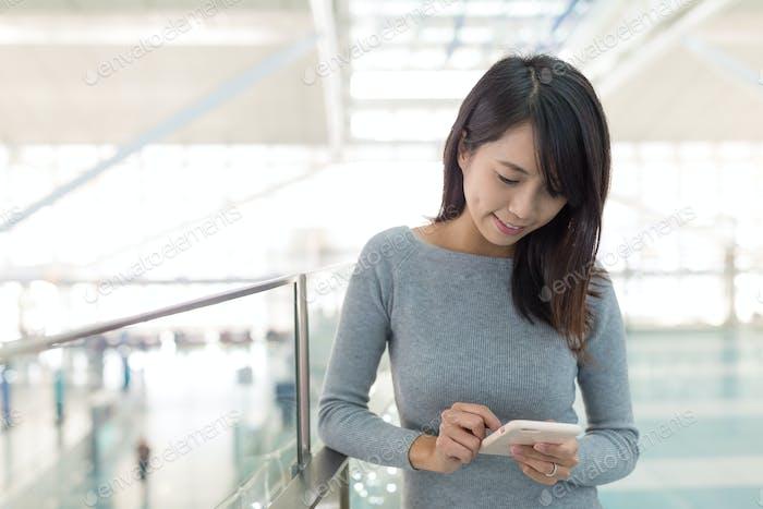 Frau, die am Handy im Flughafen arbeitet