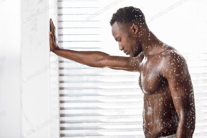 Naked Black Guy Taking Shower Washing Body In Modern Bathroom