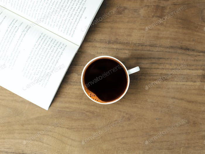 top view black coffee and books with wood background