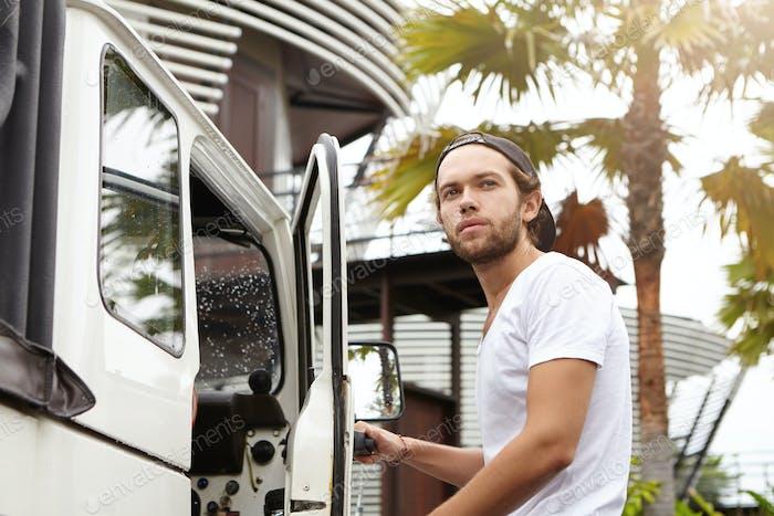 Fashionable young man with stylish beard wearing white t-shirt and baseball cap backwards looking aw