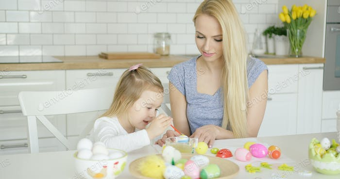 Young female and little girl painting eggs