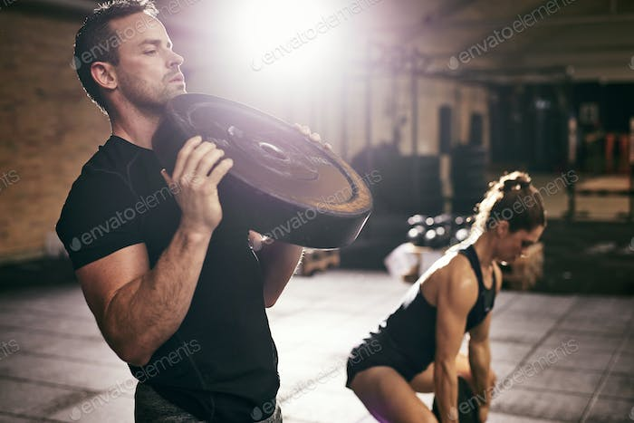 Young sportsmen having workout with weight disks