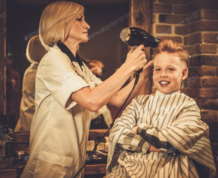 Happy little client in a barber shop