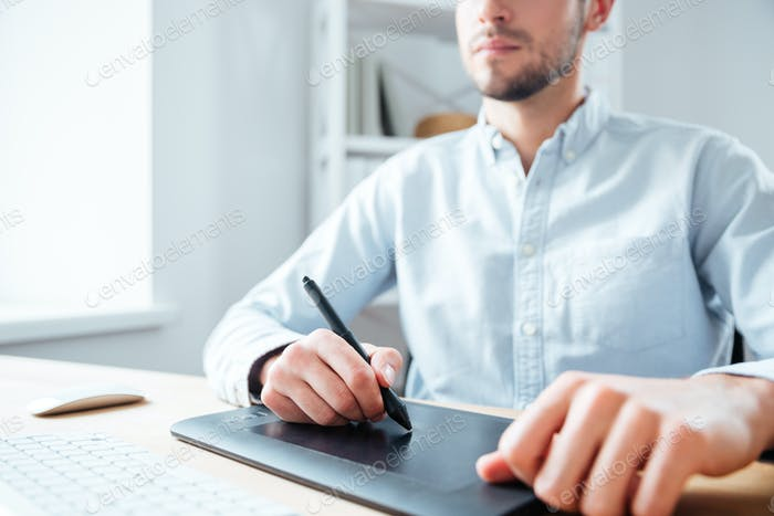 Graphic tablet used by serious young man designer in office