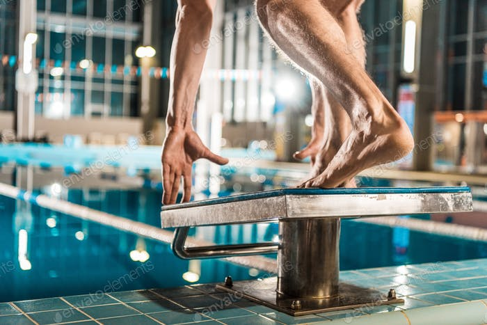 cropped view of swimmer standing on diving board ready to jump into competition swimming pool