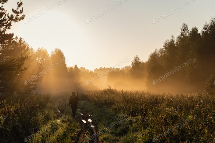 Bird Hunter at Sunrise going for hunt in a forest with his shotgun rifle