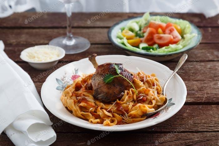 Geschmortes Kaninchenbein in Tomatensauce mit hausgemachter Pasta, dunkler rustikaler Hintergrund