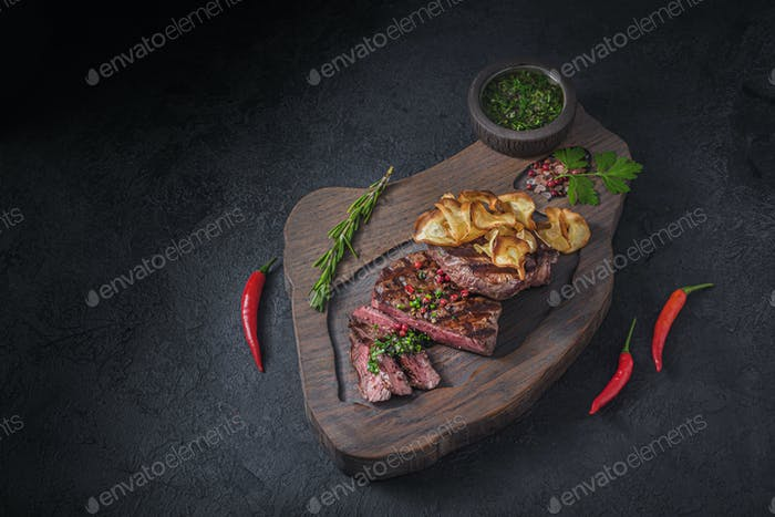 Grilled and sliced beek steak with crispy chips, copy space