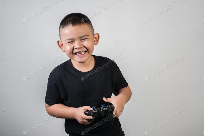 Happy boy play game computer with a controller in studio photo
