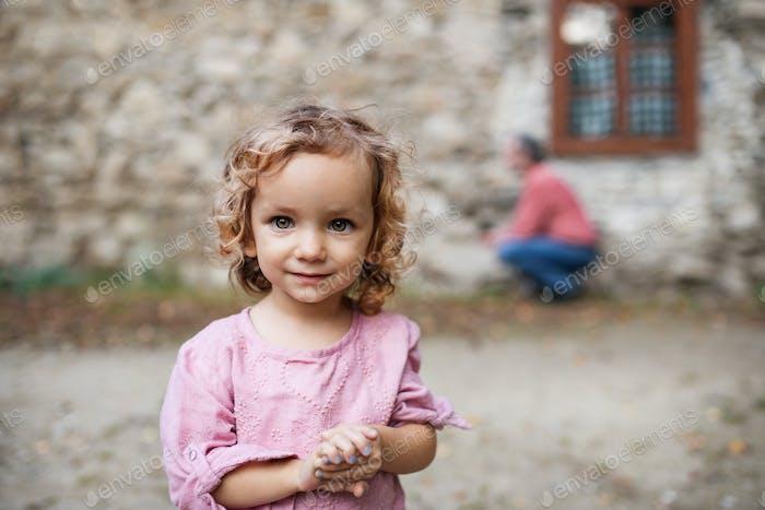 Ein kleines Mädchen steht vor dem alten Steinhaus, Blick auf die Kamera