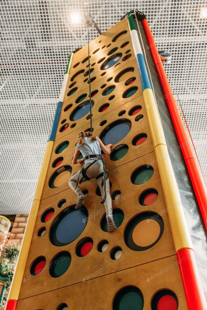 Funny girl climbing walls in children game center