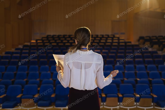 Beautiful Caucasian businesswoman practicing and learning script while standing in the auditorium