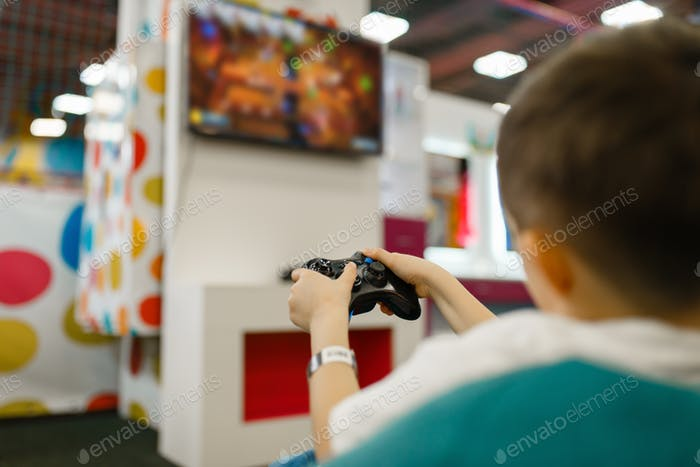 Boy plays a game console in entertainment center