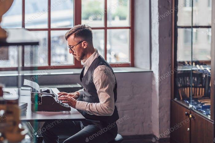 Working man with a retro typewriter