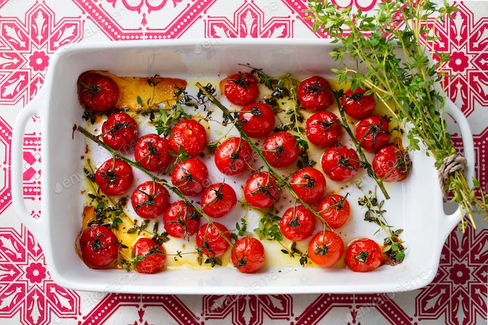 Roasted Cherry Tomatoes with Herbs in Baking Dish. Top view.