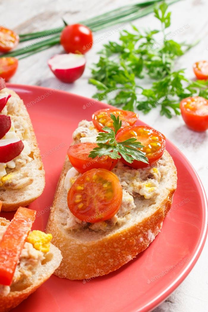 Nahaufnahme von Sandwiches oder Baguette mit Makrele oder Thunfischpaste auf Teller, gesunde Ernährung