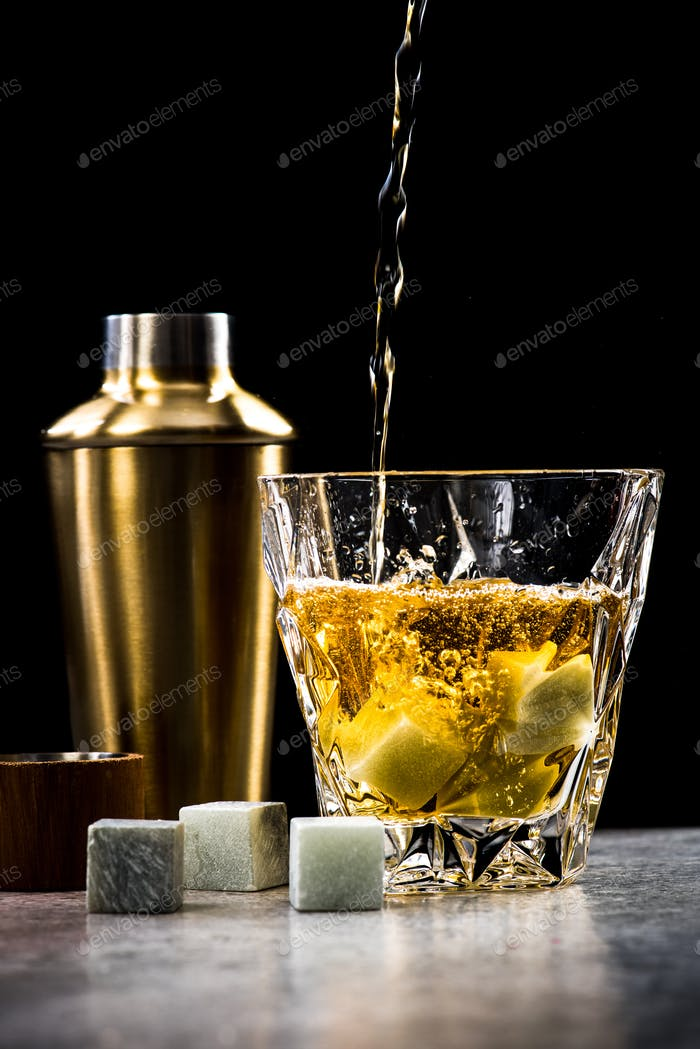 Pouring whisky or alcohol into crystal glass on bar