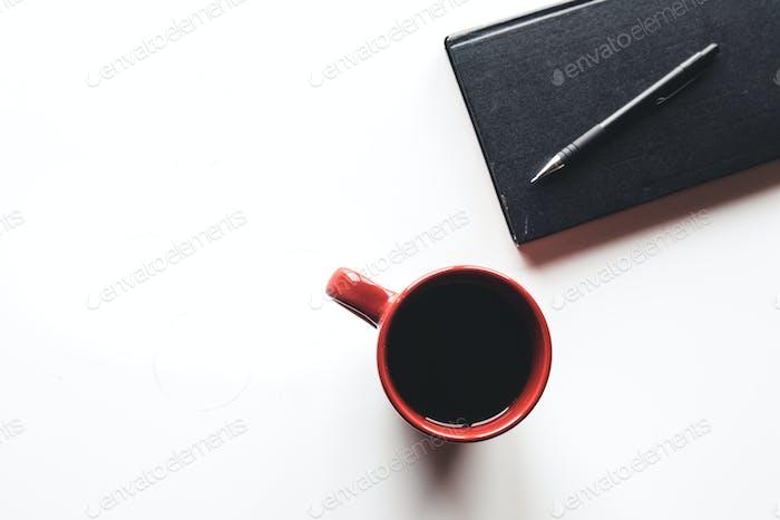 Blanko-Organizer mit Stift und leeren und vollen roten Kaffeetassen. Isoliert auf weißem Hintergrund