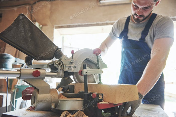 Master in a work suit using a grinder on a sawmill