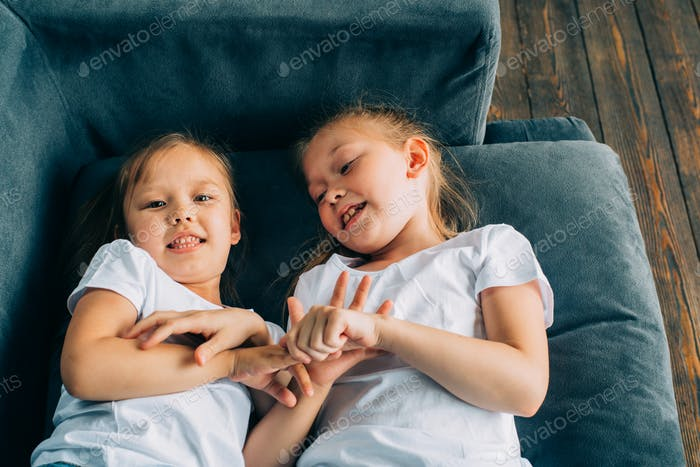 Children playing. Two girls sisters friends hug and laugh home
