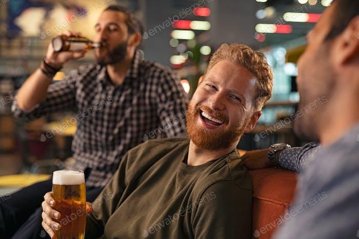 Amigos riendo y bebiendo cerveza de barril