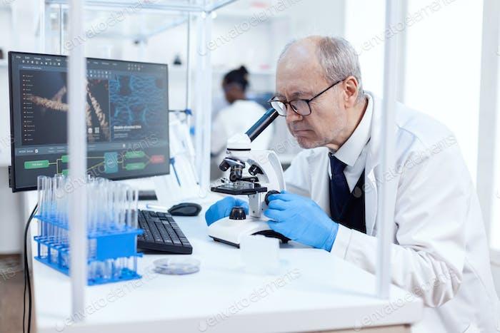 Senior scientist in chemistry laboratory uses microscope