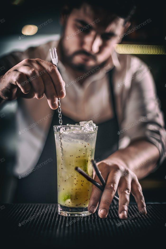 Barkeeper rührt Cocktail