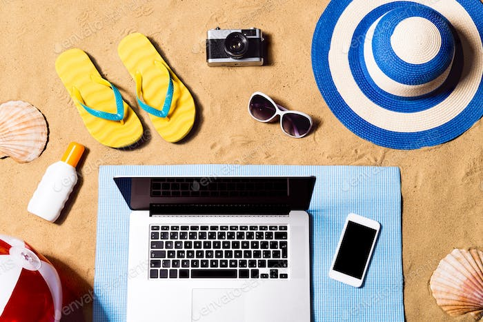 Summer vacation composition. Sandals, hat, laptop and smartphone