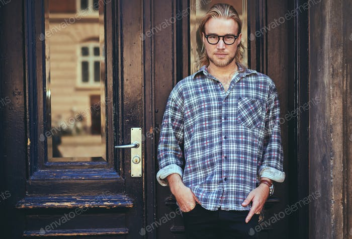 Portrait of a smart serious young man standing against building