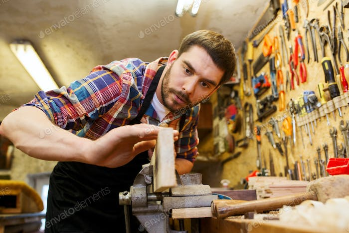 carpenter working with plane and wood at workshop