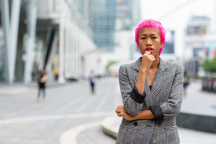 Young rebellious Asian businesswoman with pink hair thinking in the city streets
