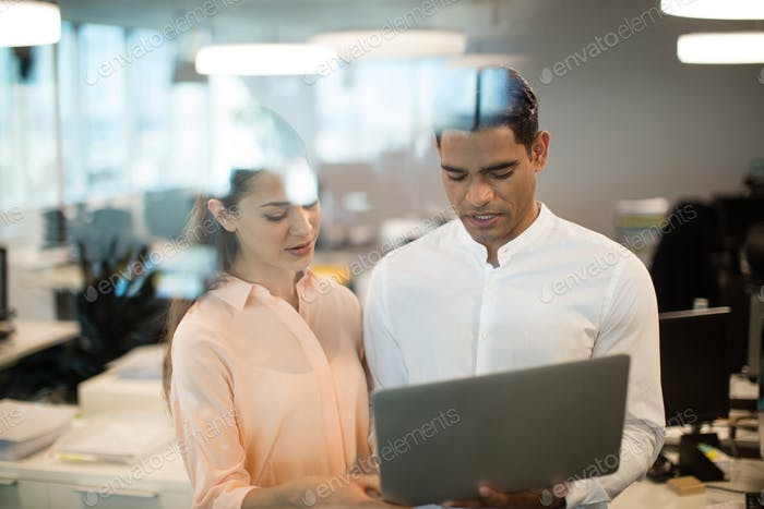 Colleagues discussing over laptop in office