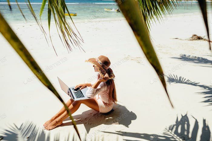 freelancer woman with laptop on beach