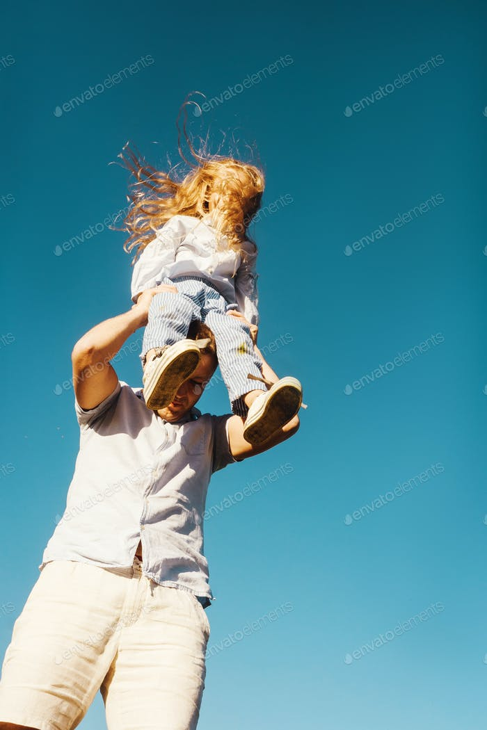Father and daughter on sky background.