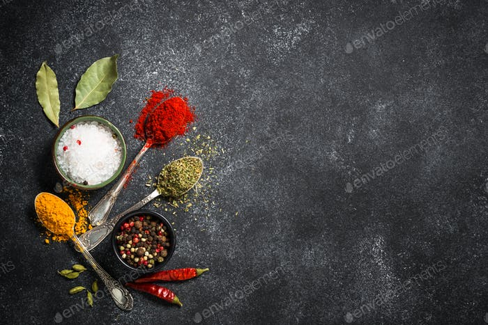 Spices, sea salt and pepper on black stone background.