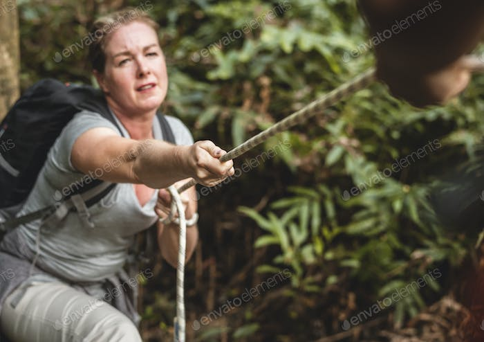 Woman climbing up a rope