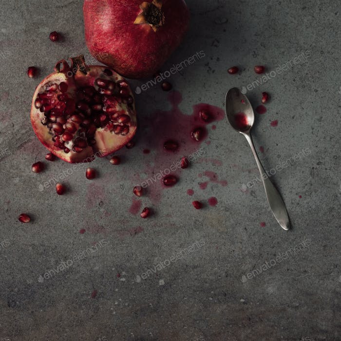 Red pomegranate fruit on dark background. Minimal flat lay concept.