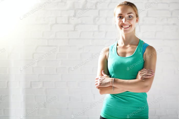 Portrait of happy smiling caucasian young sports woman against w