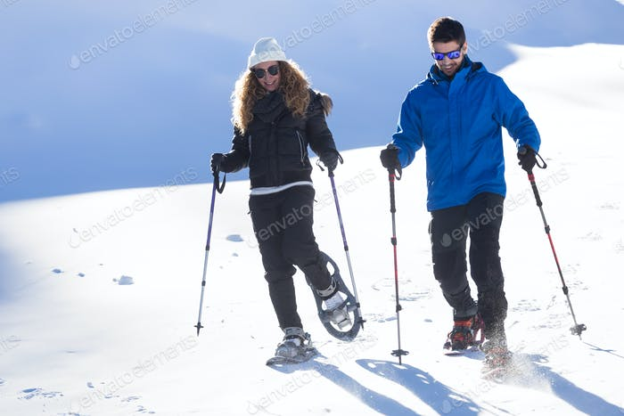 Young couple walking in snowshoes over winter background.