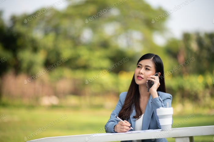 Happy young woman using smartphone in the park, green office concept outdoor