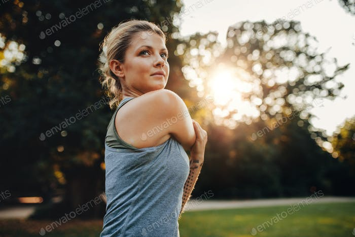 Beautiful young woman exercising in the park