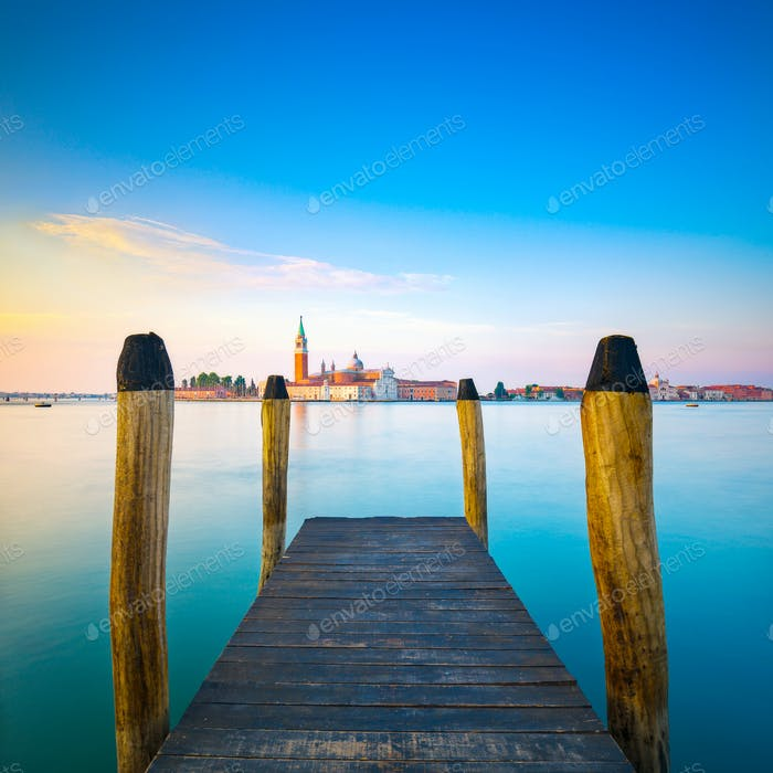 Venice lagoon, wooden pier or jetty and  poles and church on bac