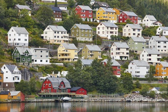 Traditional norwegian fjord village with colored houses, forest and harbor.