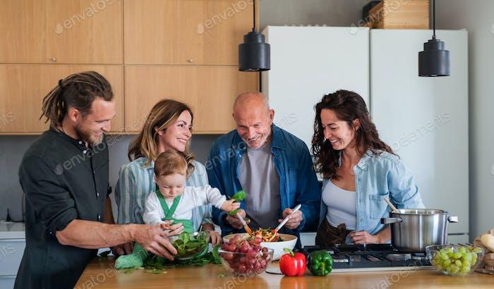 Happy multigeneration family indoors at home preparing vegetable salad