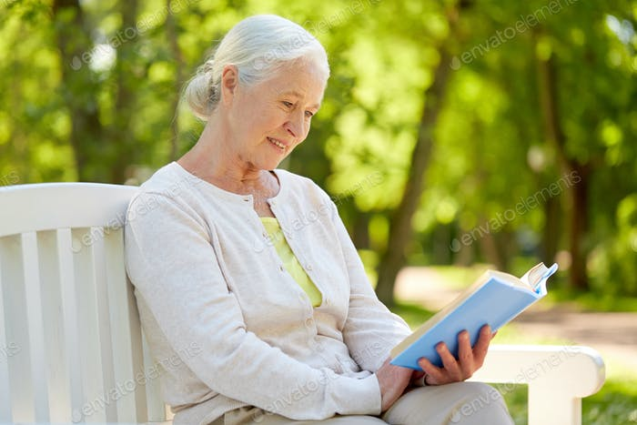 happy senior woman reading book at summer park
