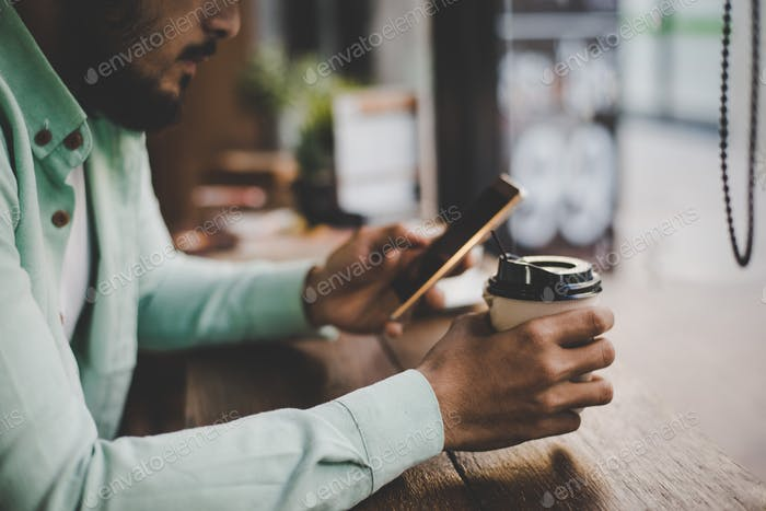 Hipster junger gutaussehender Mann benutzt sein Smartphone, während er an der Theke am Café-Hintergrund sitzt.