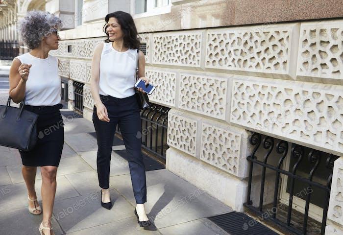 Two female work colleagues walking in the street talking